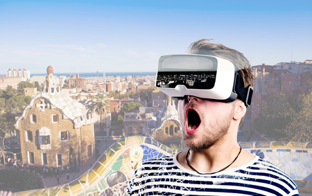 Photo pour Hipster man in striped black and white sweatshirt wearing virtual reality goggles. Park Guell, Barcelona, Spain. - image libre de droit