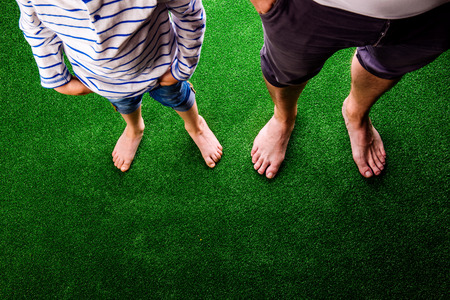 Photo for Legs of unrecognizable father and son standing, against artificial grass. Studio shot on green background. Copy space. - Royalty Free Image