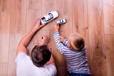 Foto de Unrecognizable father with his son playing with cars. Studio shot on wooden background. - Imagen libre de derechos