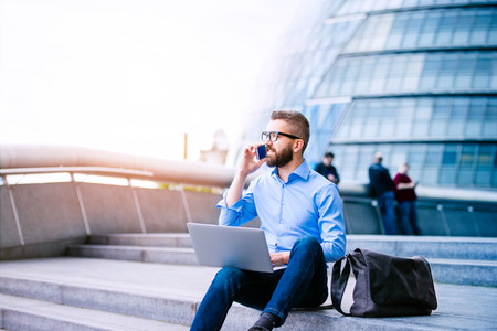 Foto de Handsome hipster manager sitting on stairs on sunny day, working on laptop, talking on a smart phone, London, City Hall - Imagen libre de derechos