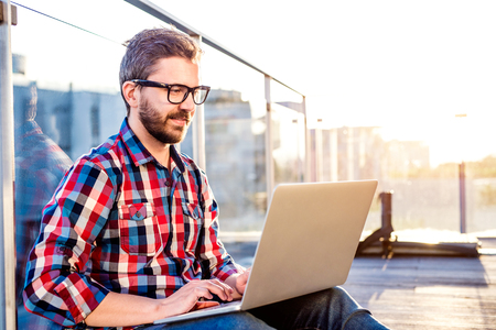 Photo for Young businessman writing on a laptop computer, sitting on the balcony - Royalty Free Image