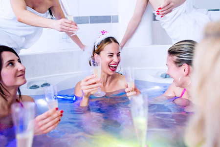 Cheerful bride and happy bridesmaids in bikinis celebrating hen party in wellness center. Women enjoying a bachelorette party.