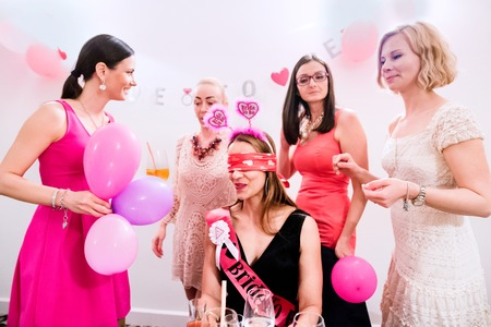 Photo for Cheerful bride and happy bridesmaids celebrating hen party with drinks. Women enjoying a bachelorette party. - Royalty Free Image