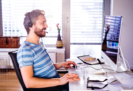 Photo for Man sitting at the desk working from home on computer, talking on the phone, headset on head, smiling - Royalty Free Image