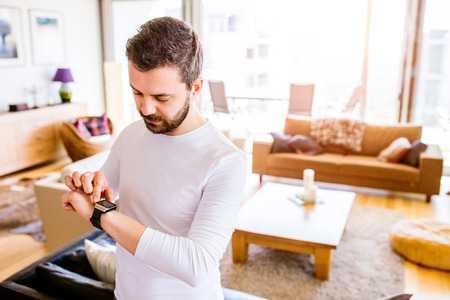 Photo for Casual hipster man working from home using smart watch, standing in living room - Royalty Free Image