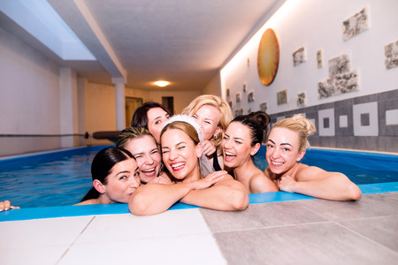Cheerful bride and happy bridesmaids in bikinis celebrating hen party in wellness center, in swimming pool. Women enjoying a bachelorette party.