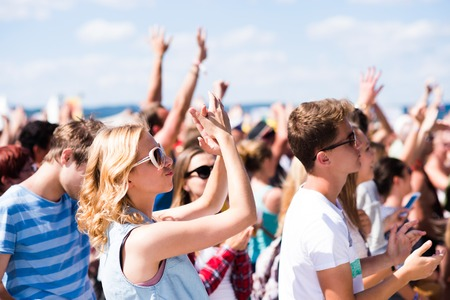 Photo pour Teenagers at summer music festival under the stage in a crowd enjoying themselves, arm raised - image libre de droit