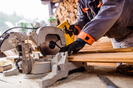 Photo for Hands of unrecognizable carpenter working. Man using circular saw to cut planks of wood for home construction - Royalty Free Image