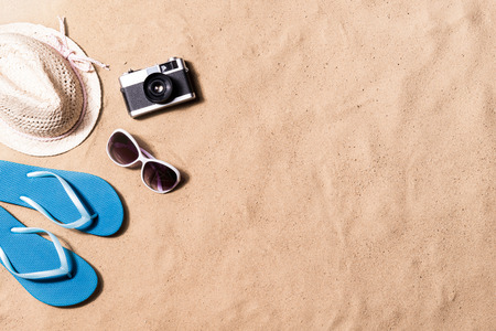 Foto de Summer vacation composition with a pair of blue flip flop sandals, hat, sunglasses and retro styled camera laid on a beach. Sand background, studio shot, flat lay. Copy space. - Imagen libre de derechos