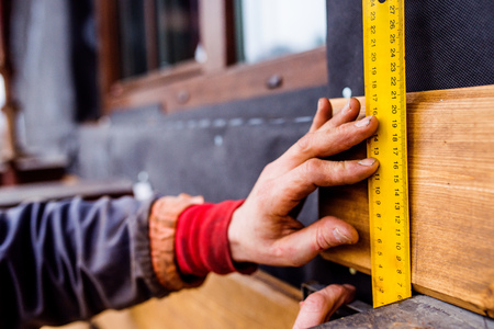Hands of unrecognizable construction worker thermally insulating house, doing wooden facade, measuring board with yellow tape measure