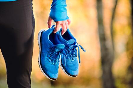 Photo pour Unrecognizable runner in blue sweatshirt holding pair of sports shoes outside in colorful sunny autumn nature. - image libre de droit