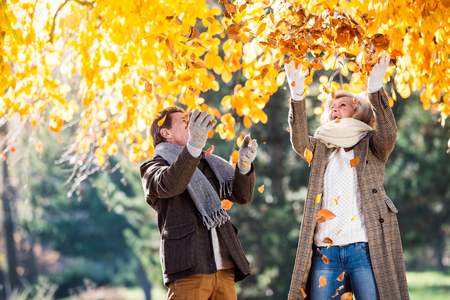 Active senior couple on a walk in autumn park throwing leaves