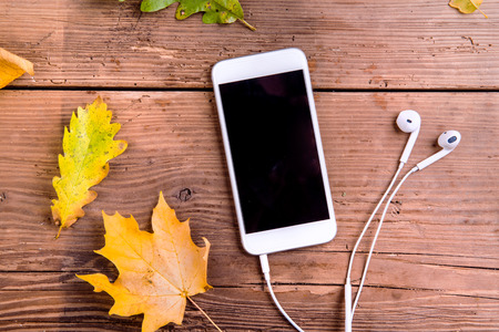 Photo pour Autumn composition. Close up of colorful oak and maple leaves and white smart phone with earphones. Studio shot on wooden background, flat lay. - image libre de droit