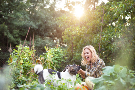 Photo pour Beautiful blond woman with her dogs in green garden - image libre de droit
