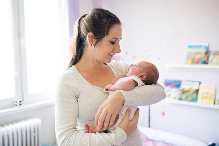 Photo for Beautiful young mother with her newborn baby son, holding him in her arms. - Royalty Free Image