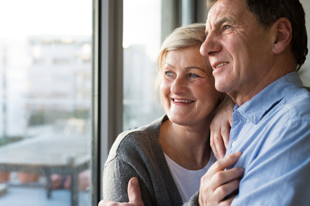 Photo pour Senior couple in living room standing at the window, hugging - image libre de droit