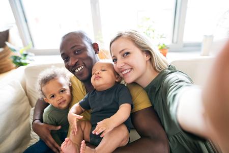 Photo pour Young interracial family with little children taking selfie. - image libre de droit