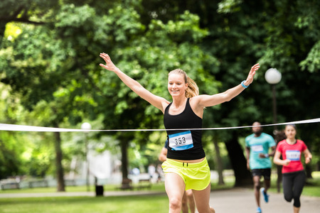 Photo pour Young woman running in the crowd crossing the finish line. - image libre de droit