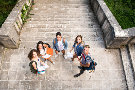 Photo pour Teenage students at the stone steps in front of university. - image libre de droit