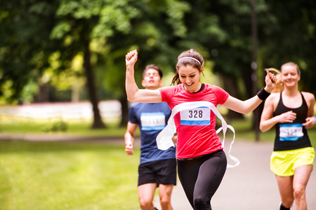 Foto de Young woman running in the crowd crossing the finish line. - Imagen libre de derechos