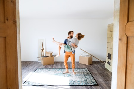 Photo pour Man carrying woman in his arms, moving in new house. - image libre de droit