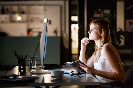 Photo pour Businesswoman in her office at night working late. - image libre de droit