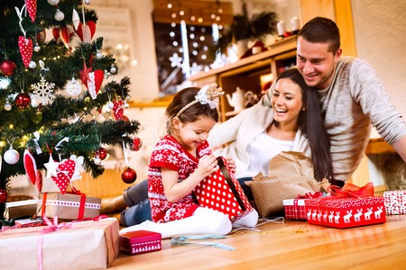 Photo pour Young family with daughter at Christmas tree at home. - image libre de droit