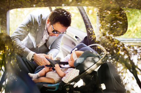 Photo pour Young father putting baby girl in the car. - image libre de droit