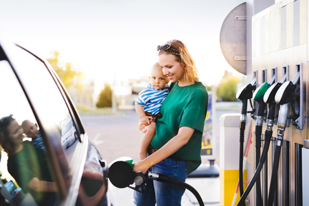 Photo pour Young mother with baby boy at the petrol station. - image libre de droit