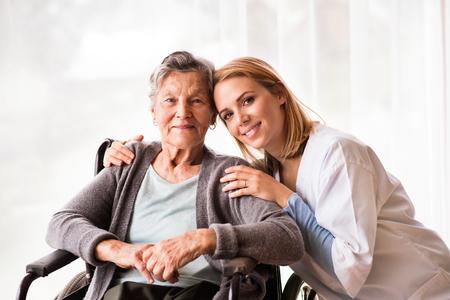 Foto de Health visitor and a senior woman during home visit. - Imagen libre de derechos