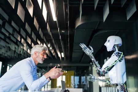 Photo pour Mature businessman or a scientist with robot. - image libre de droit