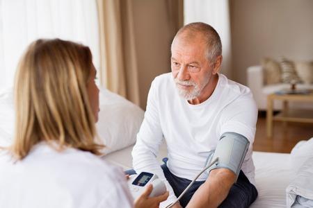 Photo pour Health visitor and a senior man during home visit. - image libre de droit