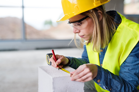 Foto de Young woman worker on the building site. - Imagen libre de derechos