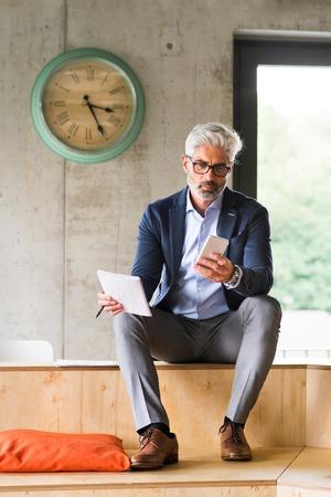 Foto de Mature businessman with smartphone in the office. - Imagen libre de derechos