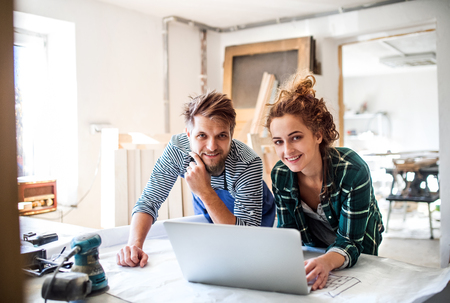 Photo for Young couple with laptop in the carpenter workroom. - Royalty Free Image
