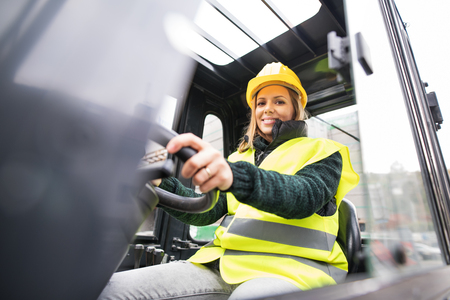 Photo pour Woman forklift truck driver in an industrial area. - image libre de droit