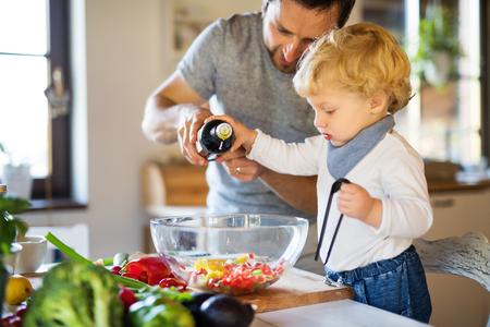 Foto de Young father with a toddler boy cooking. - Imagen libre de derechos