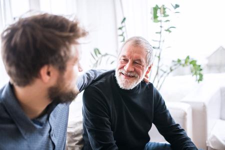Foto de Hipster son and his senior father at home. - Imagen libre de derechos