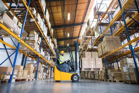 Foto de Warehouse man worker with forklift. - Imagen libre de derechos