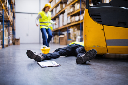 Photo for An injured worker after an accident in a warehouse. - Royalty Free Image