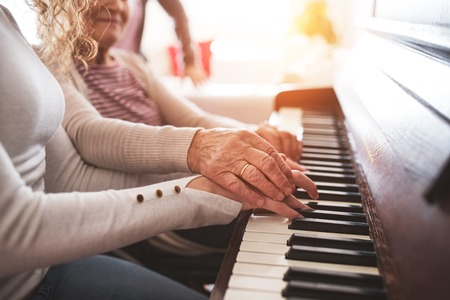 Photo pour A girl with grandmother playing the piano. - image libre de droit