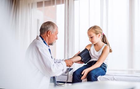 Photo pour Senior doctor checking a small girl in his office. - image libre de droit