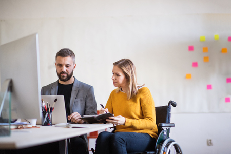 Photo for Two business people with wheelchair in the office. - Royalty Free Image