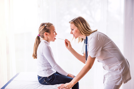 Photo pour Young female doctor examining a small girl in her office. - image libre de droit
