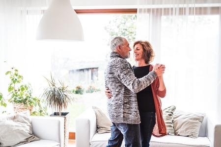 Photo pour Senior couple relaxing at home, dancing. - image libre de droit