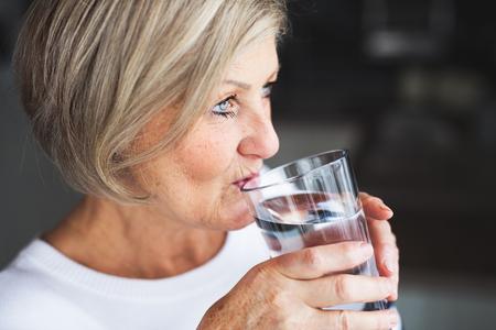Foto de Senior woman drinking water in the kitchen. - Imagen libre de derechos