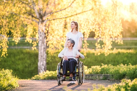 Photo pour Elderly grandmother in wheelchair with granddaughter in spring nature. - image libre de droit