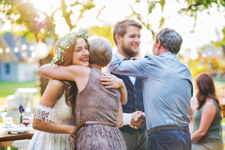 Foto de Guests congratulating bride and groom at wedding reception outside in the backyard. - Imagen libre de derechos