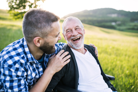 Photo for An adult hipster son with senior father in wheelchair on a walk in nature at sunset, laughing. - Royalty Free Image