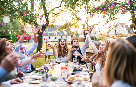 Photo pour Bride and groom with guests at wedding reception outside in the backyard. - image libre de droit